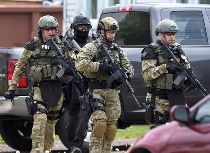 Emergency response officers check a residence in Moncton, N.B. on Thursday, June 5, 2014. Three RCMP officers were killed and two injured by a gunman wearing military camouflage and wielding two guns on Wednesday. Police have identified a suspect as 24-year-old Justin Bourque of Moncton.