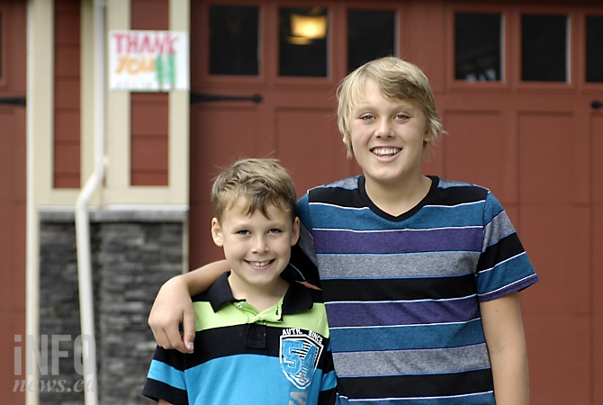 Noah Thiessen (13) and his brother Carter (10) were among those who put up thank you signs for fire crews who protected their homes during the Smith Creek fire.