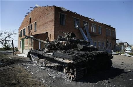 A burned Ukrainian army tank is seen near a destroyed kindergarten in the village of Kominternove, Ukraine, Saturday, Sept. 6, 2014.