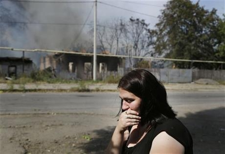 A local woman sits and cries in front of her burning house after shelling in Donetsk, eastern Ukraine, Sunday, Sept. 7, 2014.