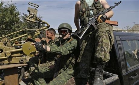 Pro-Russian rebels sit in their car with a heavy machine gun in Donetsk, eastern Ukraine, Sunday, Sept. 7, 2014.