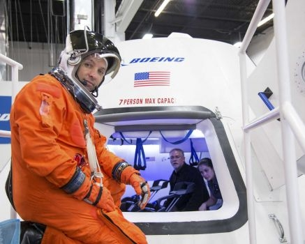 In this undated image provided by NASA, astronaut Randy Bresnik prepares to enter The Boeing Company's CST-100 spacecraft for a fit check evaluation at the company's Houston Product Support Center. On Tuesday, Sept. 16, 2014, NASA will announce which one or two private companies wins the right to transport astronauts to the International Space Station. The deal will end NASA's expensive reliance on Russian crew transport. The contenders include SpaceX, Sierra Nevada Corp., and Boeing.
