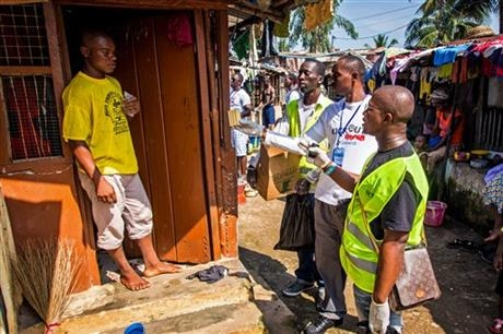 Health worker volunteers talk to a resident to distribute bars of soap and information about Ebola in Freetown, Sierra Leone, Saturday, Sept. 20, 2014.