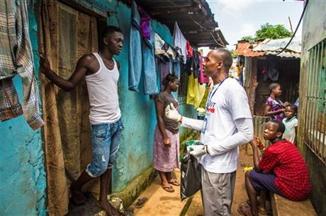 A health worker volunteer talks with a resident on how to prevent and identify the Ebola virus in others, and distributes bars of soap in Freetown, Sierra Leone, Saturday, Sept. 20, 2014.