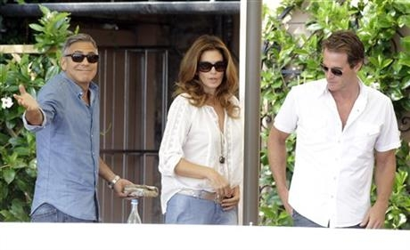 George Clooney, left, Cindy Crawford and her husband Rande Gerber walk in the garden of the Cipriani hotel in Venice, Italy, Saturday, Sept. 27, 2014.