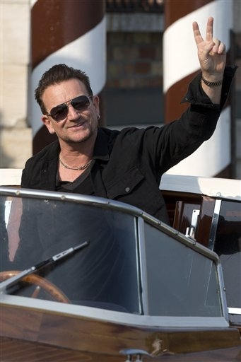 Bono Vox gives the v-sign as he arrives at the Cipriani hotel in Venice, Italy, Saturday, Sept. 27, 2014.