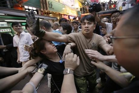 A woman is protected from the crowd by pro-democracy student protesters after a scuffle with local residents in Mong Kok, Hong Kong, Saturday, Oct. 4, 2014. Friction between pro-democracy protesters and opponents of their weeklong occupation of major Hong Kong streets persisted Saturday as police denied they had any connection to criminal gangs suspected of inciting attacks on largely peaceful demonstrators.