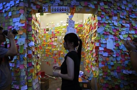 A pro-democracy supporter walks past a wall covered with messages of support, Saturday, Oct. 4, 2014 in Hong Kong.