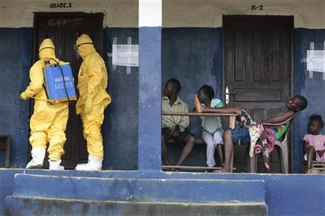Residents watch members of the ambulance service disinfect a room as they pick up six suspected Ebola sufferers.