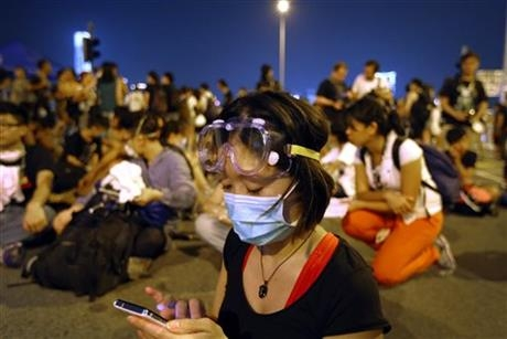A student pro-democracy protester monitors the news on her smartphone as she and others sit outside Hong Kong's Chief Executive Leung Chun-ying's office, Sunday, Oct. 5, 2014 in Hong Kong.
