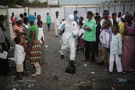 A medical worker sprays people being discharged from a treatment center in Monrovia, Liberia.