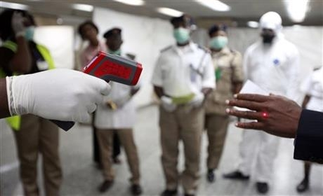 A health official uses a thermometer at the Airport in Lagos, Nigeria.