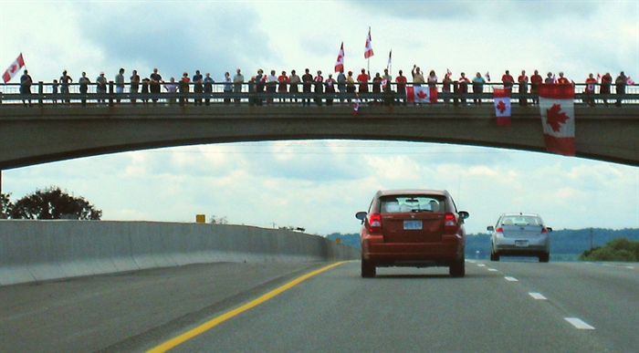 On August 24, 2007, the portion of the highway between Glen Miller Road in Trenton and the Don Valley Parkway/Highway 404 Junction in Toronto was designated the Highway of Heroes. This portion of road is travelled by funeral convoys for fallen Canadian Forces personnel from CFB Trenton to the coroner's office in Toronto. In this photo, people line the overpass in 2008 to pay respects to a fallen soldier.