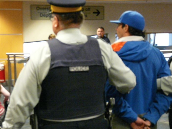 A person of interest is taken into custody at the Kelowna Airport, Saturday, Oct. 25, 2014.