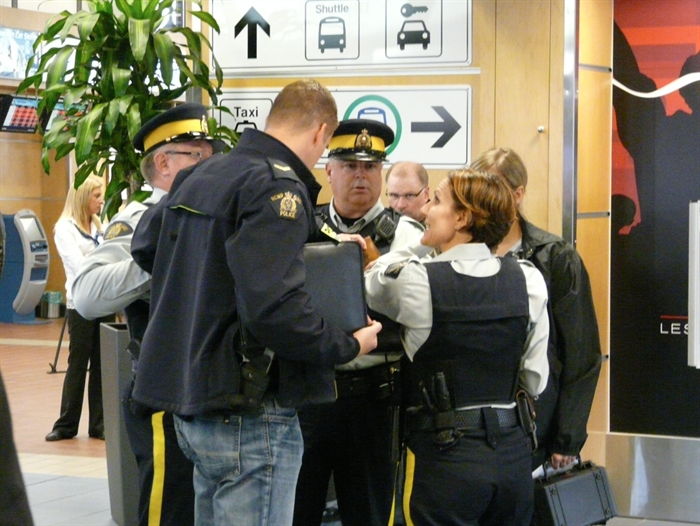 Members of the RCMP investigate a threat against a WestJet flight at the Kelowna Airport, Saturday, Oct. 25, 2014.