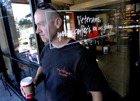 Arizona Air National Guard Lt. Col. Greg Grattop exits a Starbucks with his free coffee, Tuesday, Nov. 11, 2014 in Chandler, Ariz.