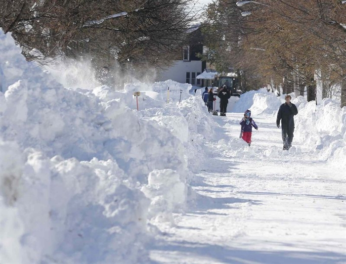 People walk along a snow-covered street in the south Buffalo area on Friday, Nov. 21, 2014, in Buffalo, N.Y.