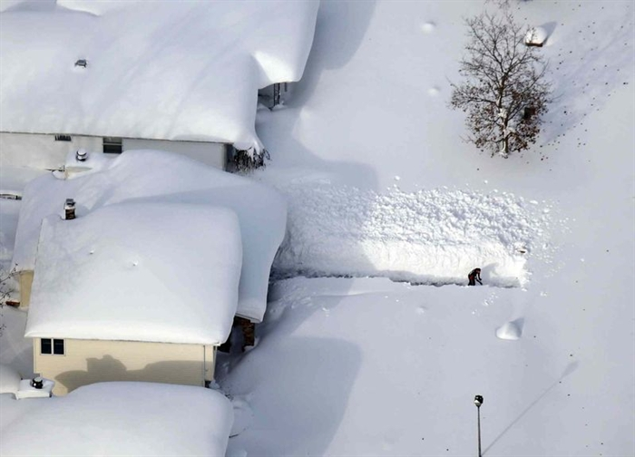 A man digs out his driveway in Depew, N.Y., Friday, Nov. 21, 2014.