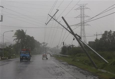 Motorists pass by toppled electrical posts during Typhoon Hagupit in the Philippines, Sunday, Dec. 7, 2014.