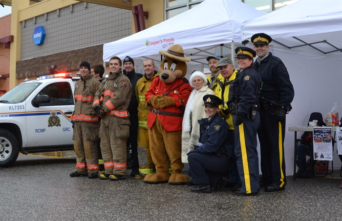 Lake Country Fire Fighters, RCMP officers and auxiliary constables and RCMP volunteers are pictured with Lake Country Food Bank manager Phyllis MacPherson and the Sgt. Sam Brown mascot.
