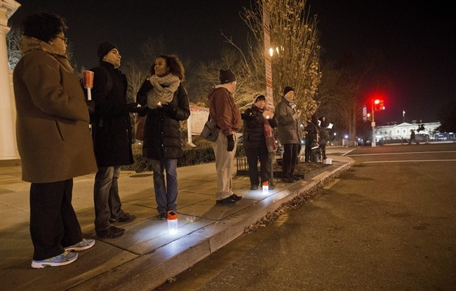 Participants stand on the curb holding candles or flashlights during a visual demonstration near the White House in response to the recent grand jury decisions not to indict police officers, Friday, Dec. 12, 2014, in Washington.