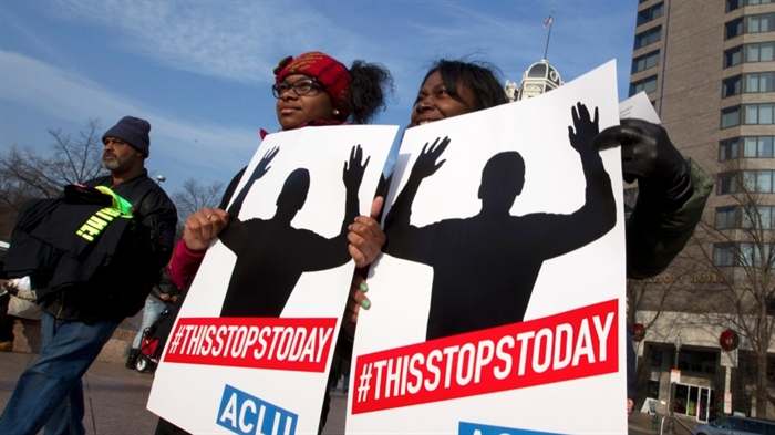 Melissa W. Green, right, and her daughter, Reshae Green, hold up their signs at Freedom Plaza during the Justice for All march and rally on Pennsylvania Avenue in Washington on Saturday, Dec. 13, 2014.