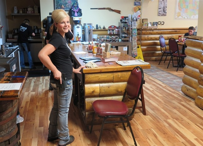 Waitress Dusty Sheets poses in Shooters Grill on Aug. 22, 2014, a restaurant in Rifle, Colo., where the staff are armed with handguns. So are many of the patrons.