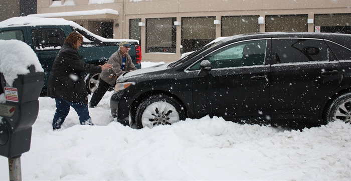 Harry and Bonnie Kinakin assist a motorist stuck in a parking stall in front of Penticton City Hall, Monday, Jan. 5, 2015.