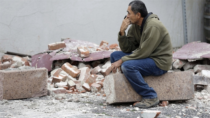 Ron Peralez, of Vacaville, Calif., sits on rubble and looks at earthquake-damaged buildings, in Napa, Calif., Monday, Aug. 25, 2014.