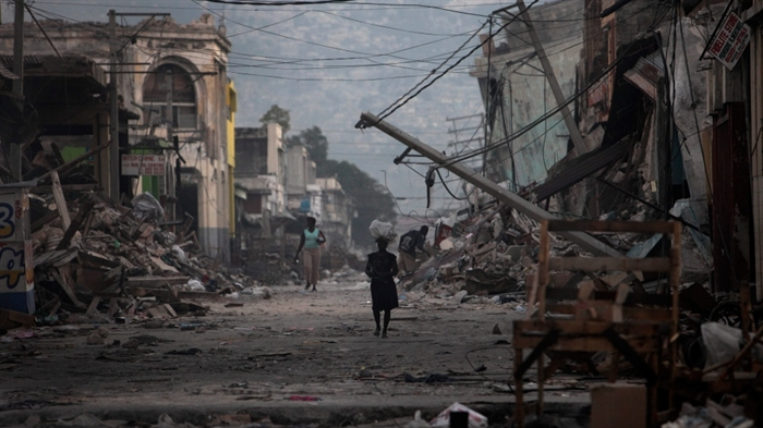 Women walk down a devastated street past the devastation caused by a 7.0-magnitude earthquake, in Port-au-Prince, Haiti, Jan. 20, 2010.