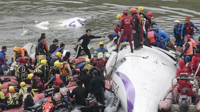 Emergency personnel try to extract passengers from a commercial plane after it crashed in Taipei, Taiwan Wednesday, Feb. 4, 2015. The Taiwanese commercial flight with 58 people aboard clipped a bridge shortly after takeoff and crashed into a river in the island's capital on Wednesday morning.