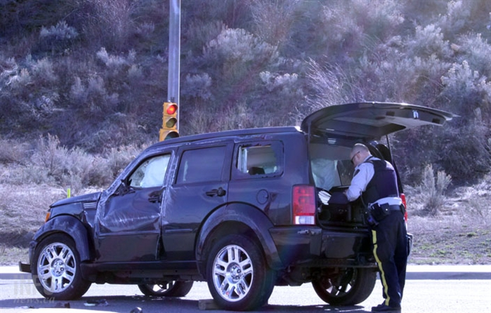 An officer searches the back of the vehicle after a driver allegedly fled