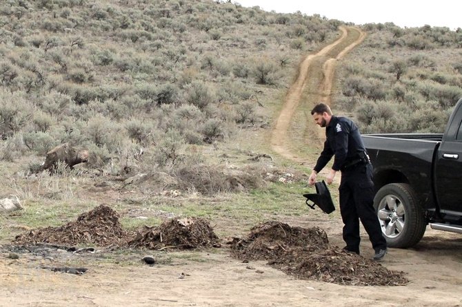 Conservation Officer Rob Armstrong checks the contents of a laptop bag dumped among a pile of garbage.