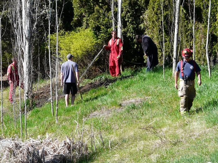 A Kelowna firefighter mops up a small grass fire with a garden hose in Brant's Creek Linear Park Sunday morning, April 19, 2015, while residents, who helped put out the fire, look on.