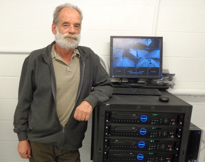 Potanicals' Cliff Stowell with a computer system that can store two years of video from 54 surveillance cameras.