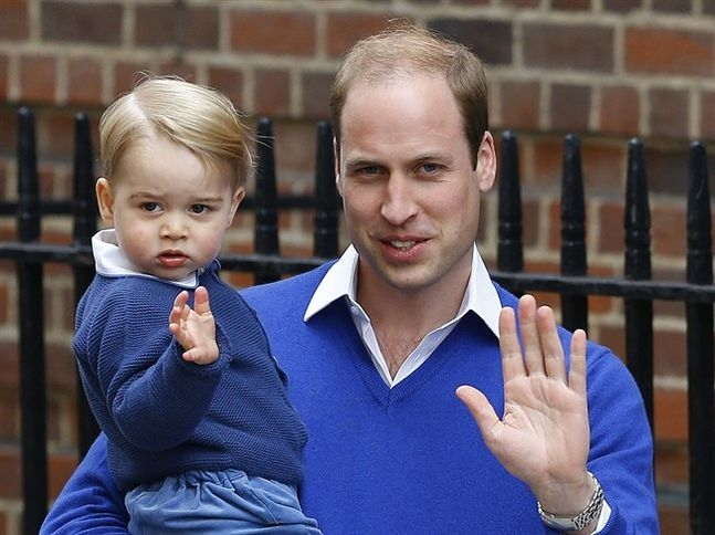 Britain's Prince William and his son Prince George wave as they return to St. Mary's Hospital's exclusive Lindo Wing, London, Saturday, May 2, 2015. William's wife, Kate, the Duchess of Cambridge, gave birth to a baby girl on Saturday morning.