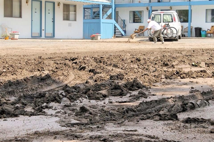 A motel worker shovels the mud from the property's parking lot.
