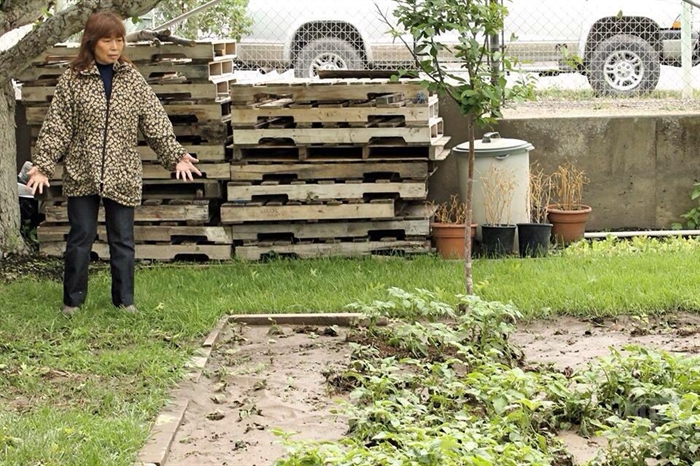 Linkwai Leung stands next to her garden covered in mud.