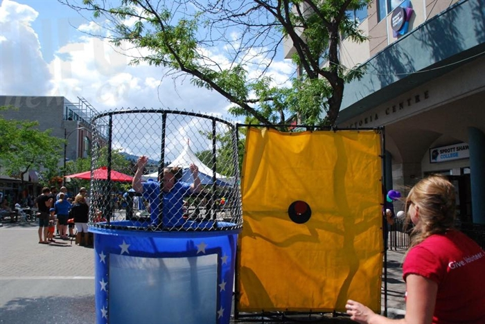 Big Brothers Big Sisters' booth complete with dunk tank, and soaking bylaw officer.