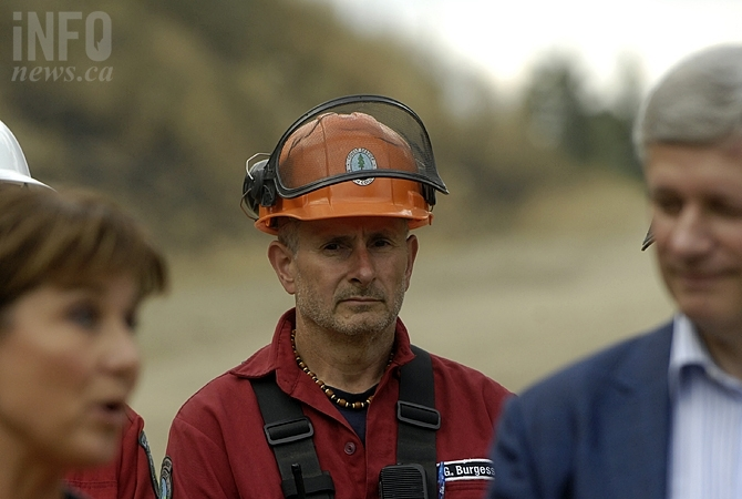A firefighter stands behind the Prime Minister and Premier Christy Clark during a staged photo op in West Kelowna last week. The story has made national headlines for refusing to name the Prime Minister.