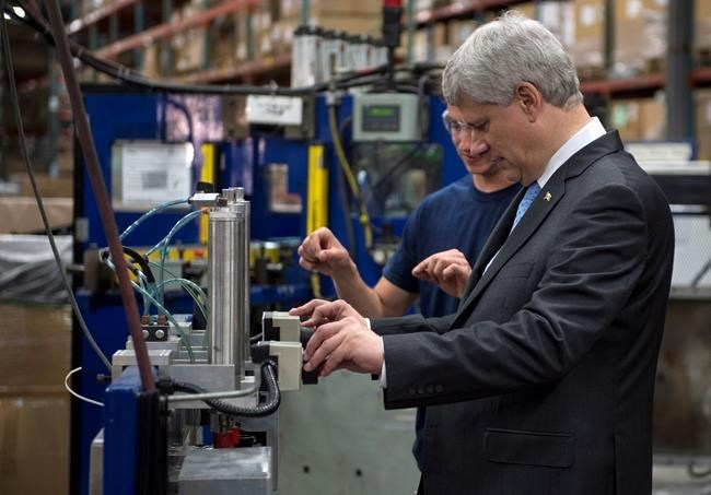 Conservative Leader Stephen Harper gets instructions on how to operate a machine that puts the finishing touch to a radiator while touring a industrial parts manufacture Monday, August 3, 2015 in Laval, Que.