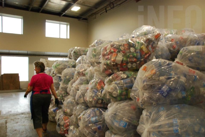 Manager Judith Jordan of General Grants Sahali walks past a mountain of recyclables collected during the Emterra Environmental strike.