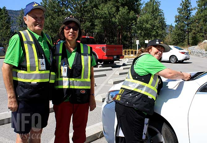 Community policing volunteers (from left to right) Nick Merluk, Carole Aoki and Sue McDougall issue auto crime prevention notices at Skaha Bluffs parking lot.