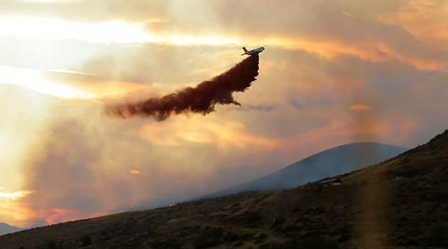 A plane drops fire retardant on a wildfire near Twisp, Wash. Wednesday, Aug. 19, 2015. Authorities on Wednesday afternoon urged people in the north-central Washington town to evacuate because of a fast-moving wildfire.