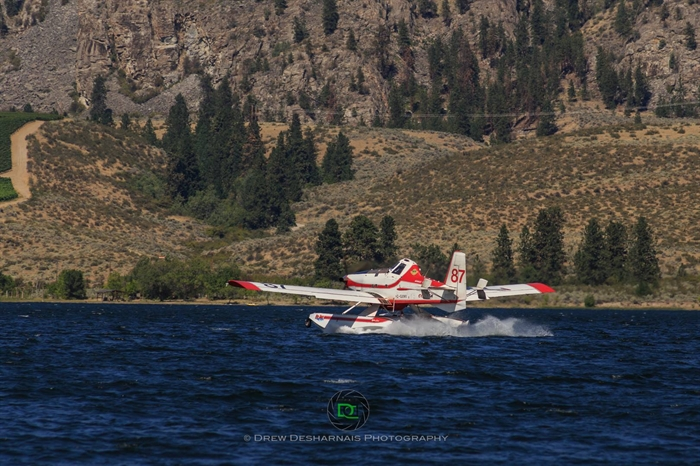 A Conair Fire Boss skimmer is filling up its water tanks on Osoyoos Lake before returning to fight the Testalinden Creek fire, Tuesday, Aug. 18, 2015.