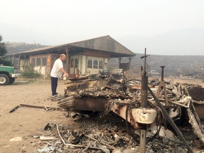 Steve Surgeon surveys the ruins after he lost everything he owned except his home in a wildfire on the outskirts of Okanogan, Wash., Sunday, Aug. 23, 2015.