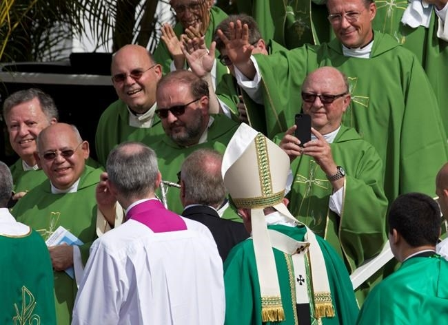 Clergy wave to and take pictures of Pope Francis after he celebrated Mass at Revolution Plaza in Havana, Cuba, Sunday, Sept. 20, 2015.