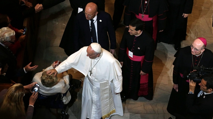 Pope Francis touches a woman in a wheelchair after he addressed a gathering in Saint Martin's Chapel at St. Charles Borromeo Seminary Sunday, Sept. 27, 2015.