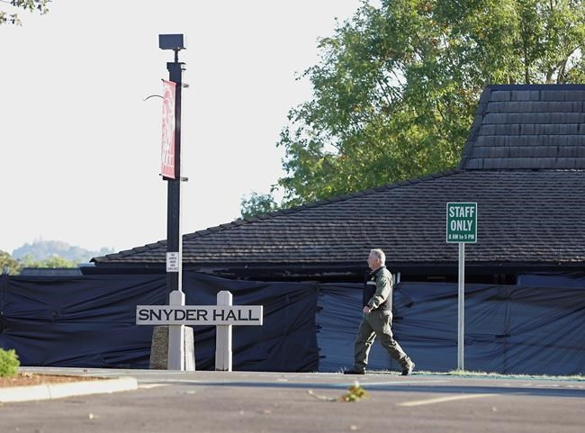 A Douglas County Sheriff's deputy walks past Snyder Hall at Umpqua Community College, Sunday, Oct. 4, 2015, in Roseburg, Ore.