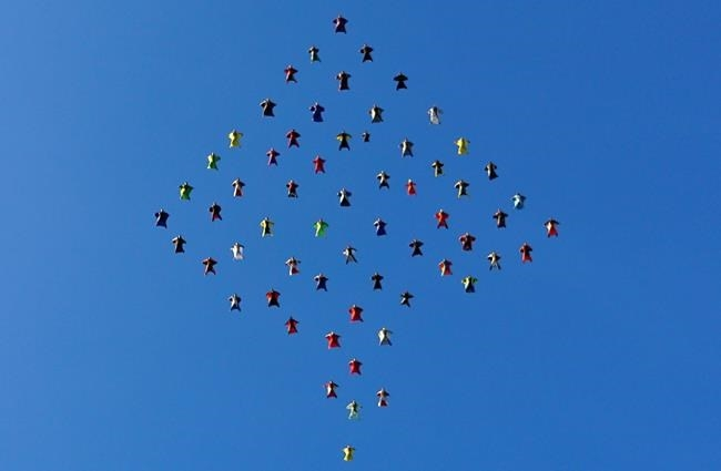 This photo taken, Oct. 17, 2015, and provided by Skydive Perris shows 61 wingsuit skydivers setting a new world record for the largest aerial formation in the sky over Perris, Calif., about 70 miles southeast of Los Angeles. Exiting from three airplanes at 13,5000 feet, flyers formed a diamond shape in flight, covering a distance of more than two miles, before dispersing at 5,500 feet. The record event included participants from 12 countries.
